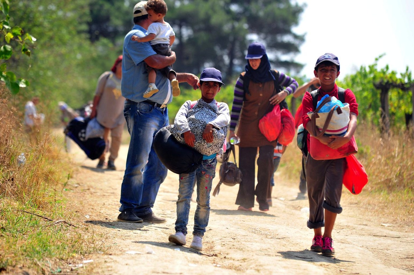 Migrant children, women and a man walk along a dusty path from the Greek border to the reception centre near the town of Gevgelija, Macedonia. Europe is struggling to handle the global migrant crisis exacerbated by conflict in the Middle East and North Af