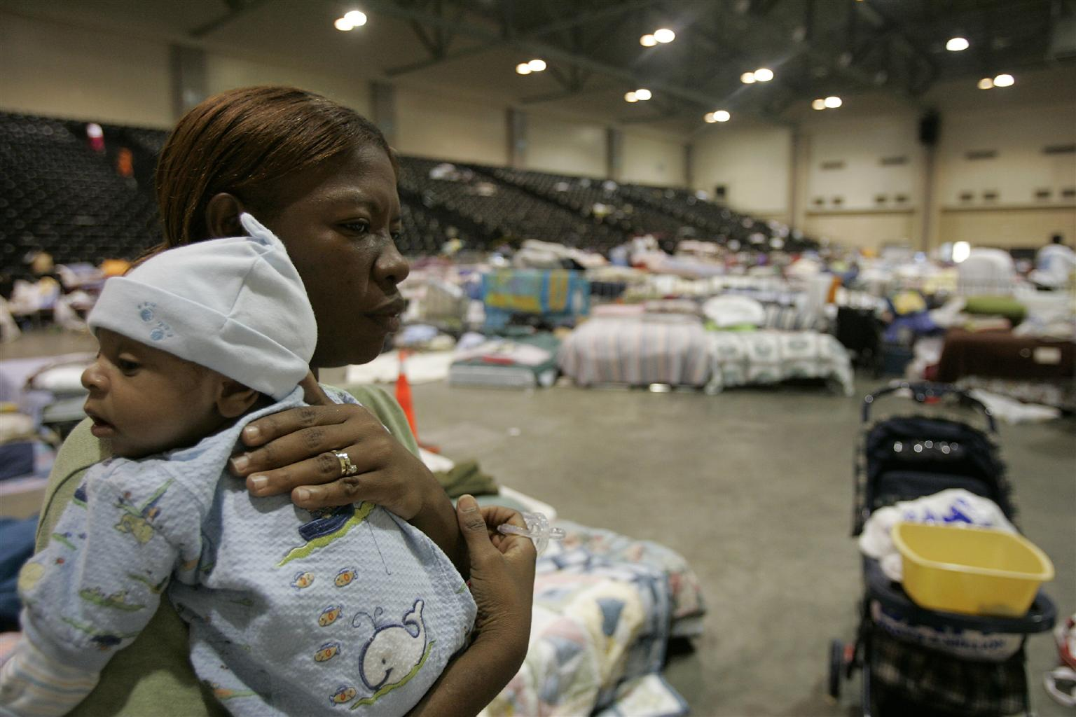 A woman carriers her grandson at a shelter for people displaced by Hurricane Katrina.