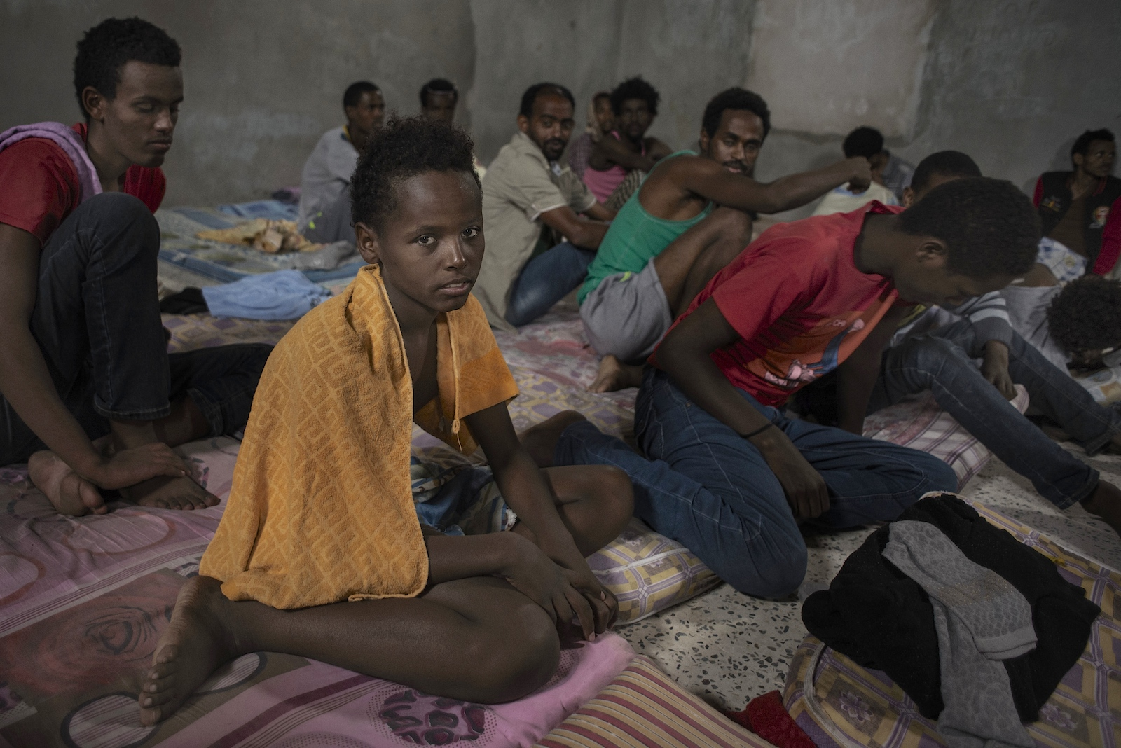 Sagga, 12 years old, and other inmates at a detention camp for migrants in Zawya, Libya.