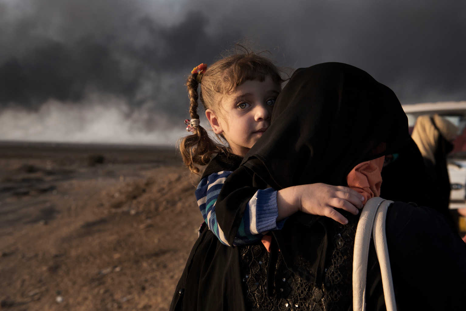 UNICEF PHOTO: A newly displaced woman carries a child at a check point in Qayyara, south of Mosul, IRAQ.