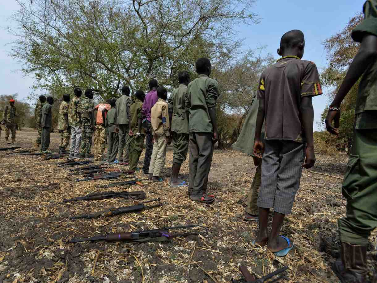 Children surrender their weapons during a ceremony formalizing their release from the SSDA Cobra Faction armed group, in Pibor, South Sudan.