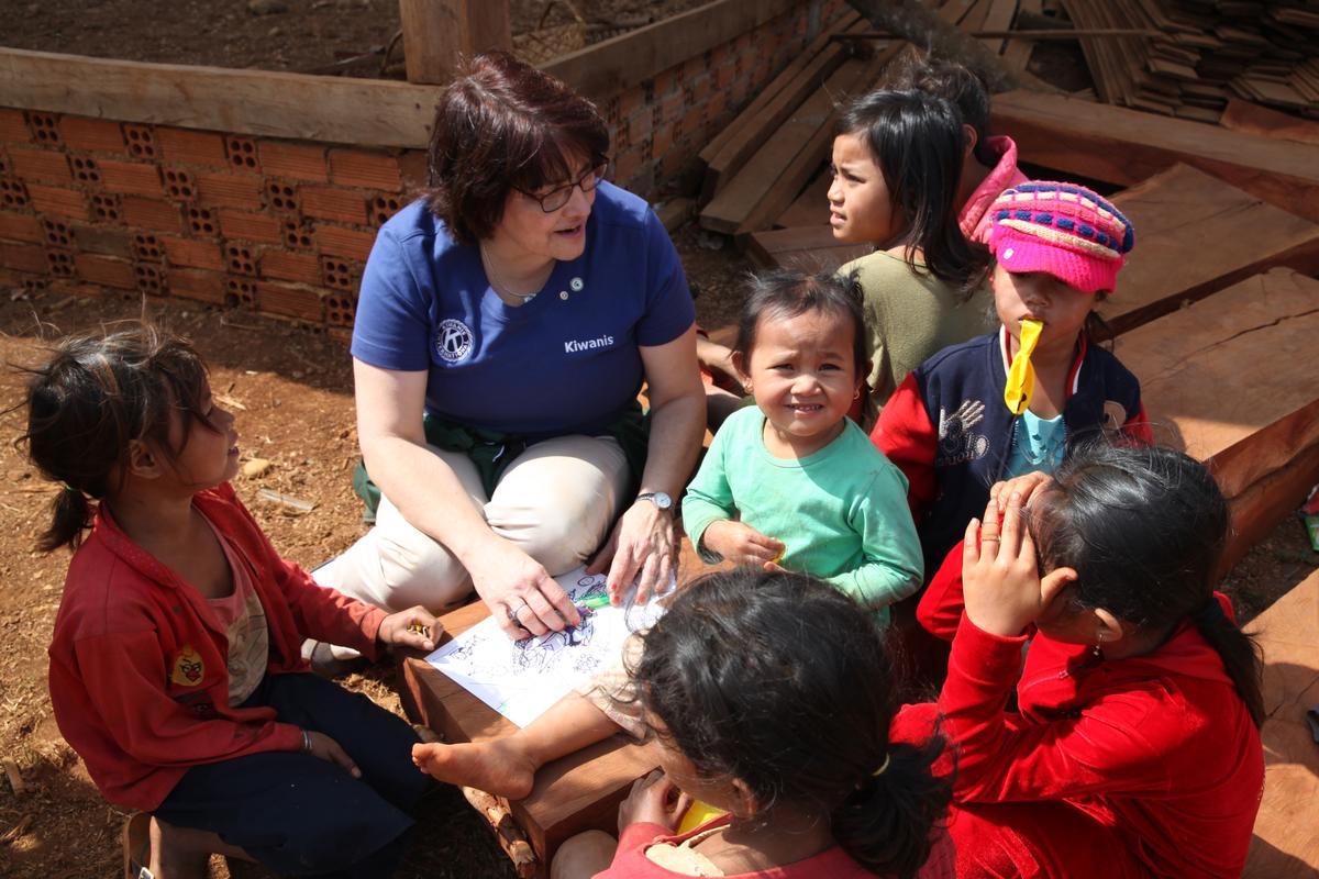 Kiwanis International President Sue Petrisin teaches children to draw on a field visit in Cambodia.