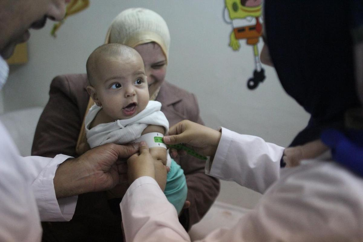 Rudania, a mother of 3, takes her 7-month-old daughter to a nutrition center in Damascus, Syria, where her mid-upper arm circumference is measured to assess her nutritional status.