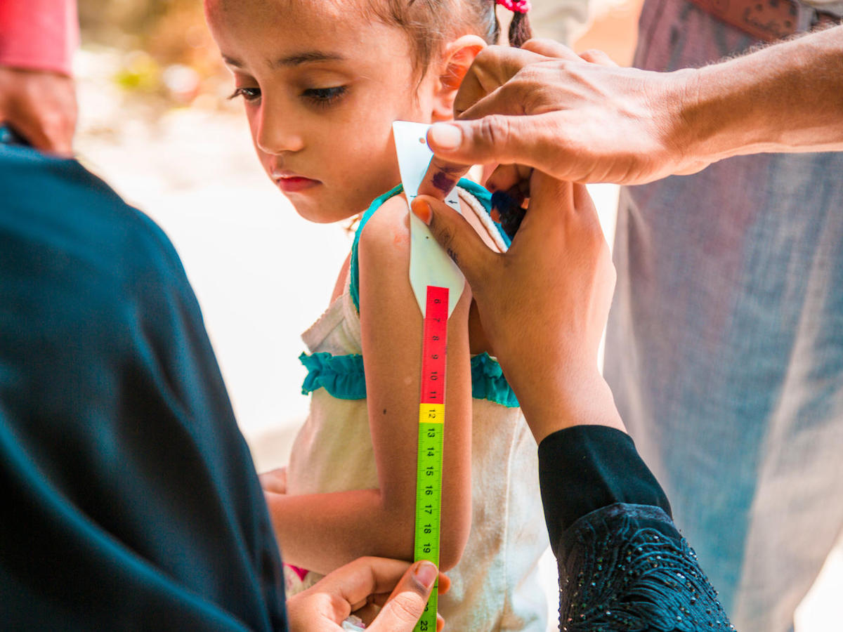 A child has her upper arm measured to screen for malnutrition as part of a door-to-door immunization campaign in Yemen in October 2017.