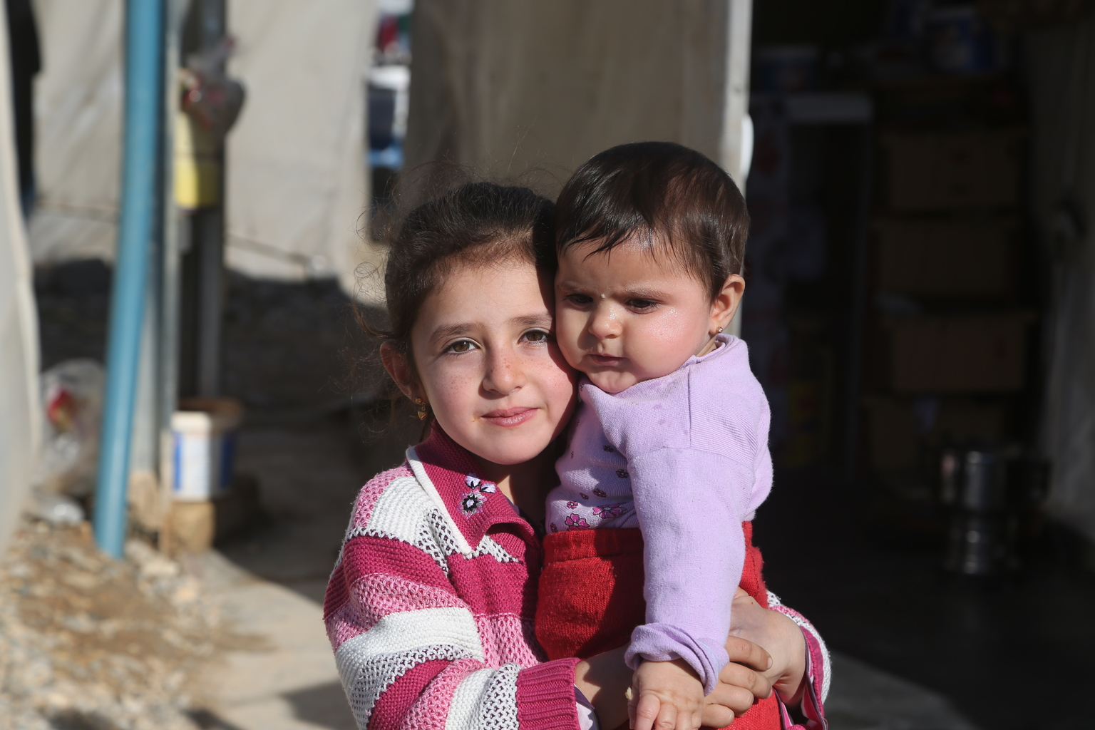 A girl carrying her baby sister in Nizip 1 refugee camp, Gaziantep, southern Turkey. Nizip 1 camp is home to over 10,000 Syrian refugees