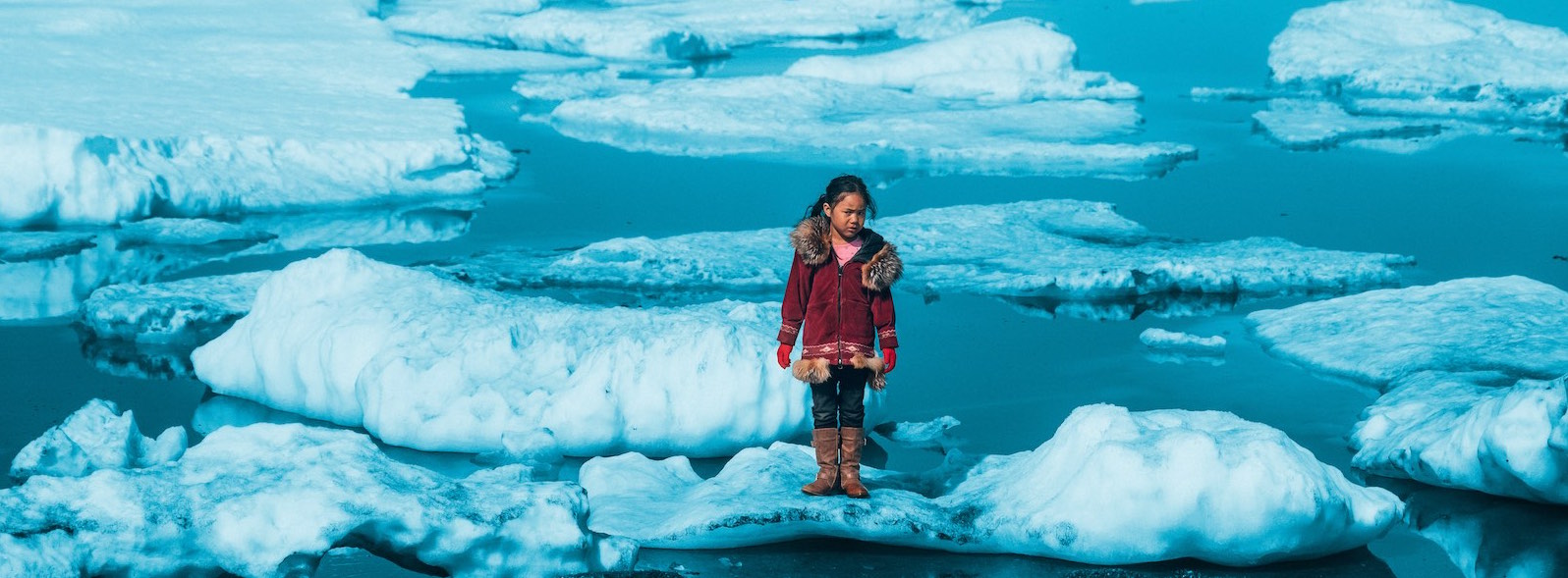 Iñupiat girl Amaia, 11, standing on a ice floe on a shore of the Arctic Ocean in Barrow, Alaska in the United States of America. The anomalous melting of the Arctic ice is one of the many effects of global warming.