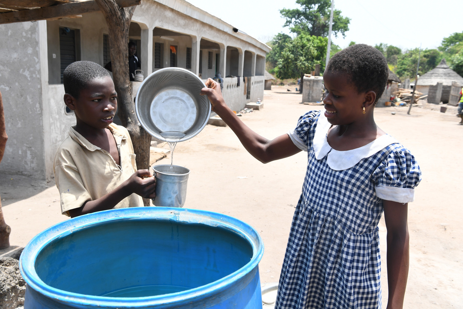 Two young children drinking safe water in the village of Kotouba, in northwest Côte d'Ivoire.