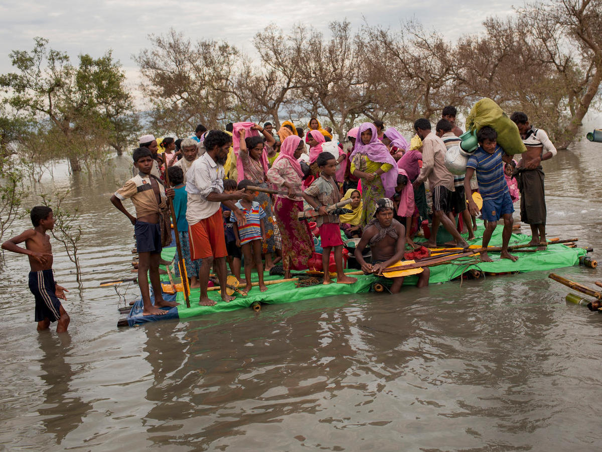 Rohingya refugees crowd onto a makeshift raft to cross the Naf River that separates Myanmar and Bangladesh, in November 2017.
