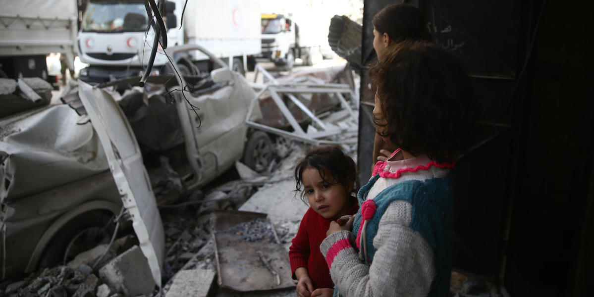 Children watch as a joint UNICEF, United Nations and Syrian Arab Red Crescent convoy of 46 trucks transporting food aid arrive in Eastern Ghouta on March 5, 2018.