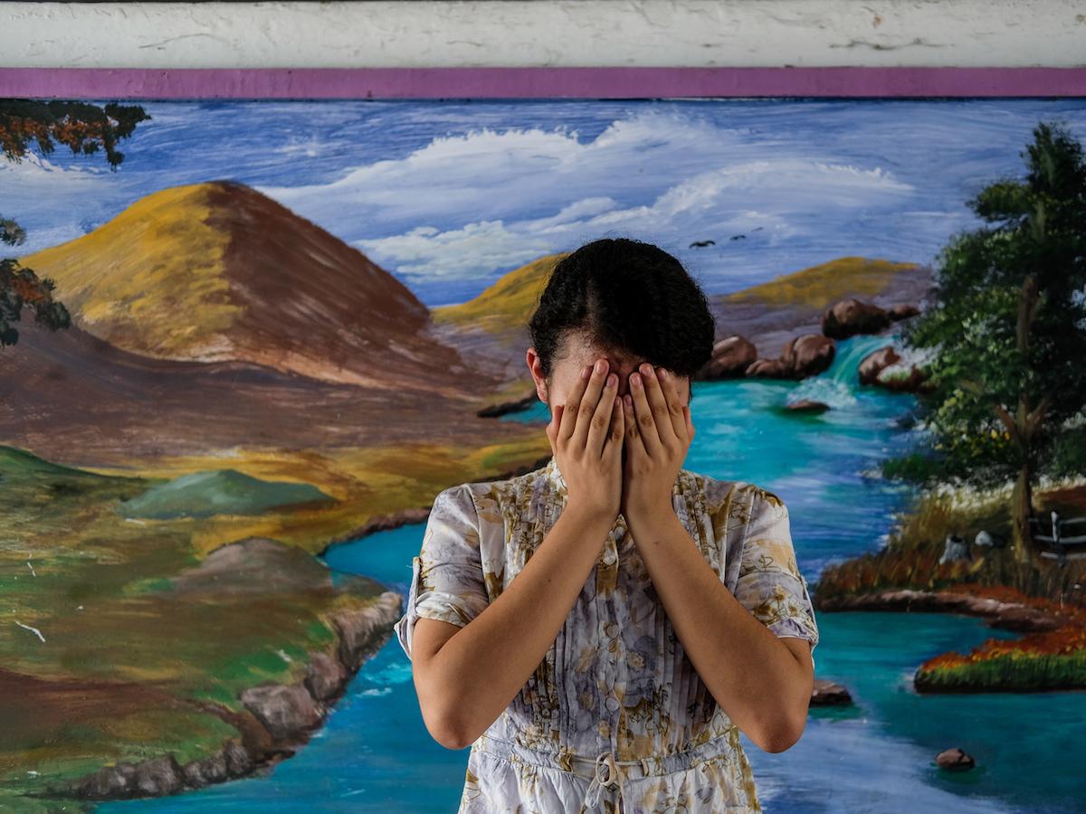 Patricia, 14, covers her face at a school in San Salvador, El Salvador.
