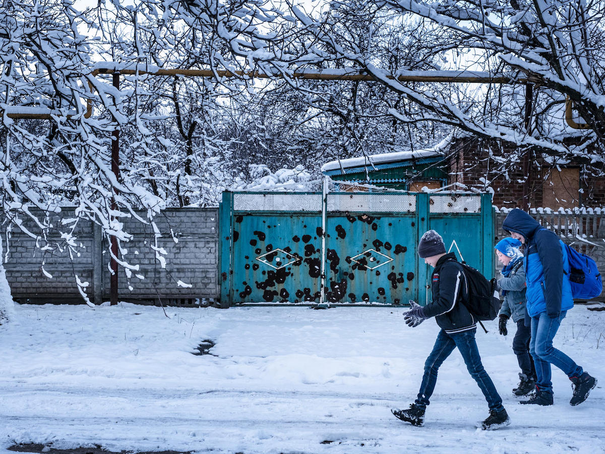 Twelve-year-old Sasha, left, walks to school in the town of Avdivka, Donetsk Oblast, Ukraine, November 2017. Because of shelling and lack of heat, his school is open only three days a week.