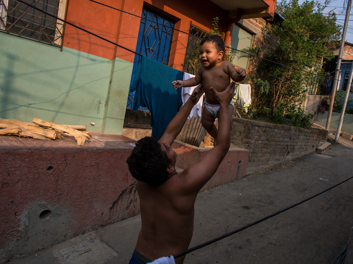 A father holds his infant son in San Salvador, El Salvador.