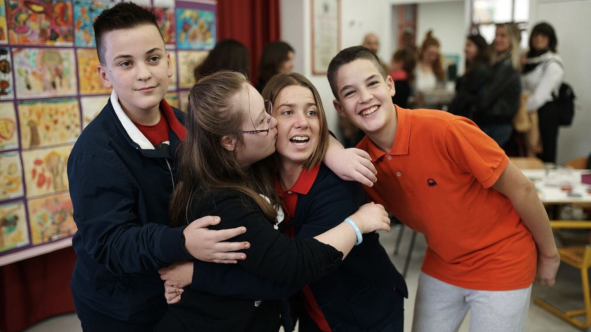 Lucy Meyer, an advocate for children with disabilities, receives a warm welcome from children during a school visit in Kosovo.