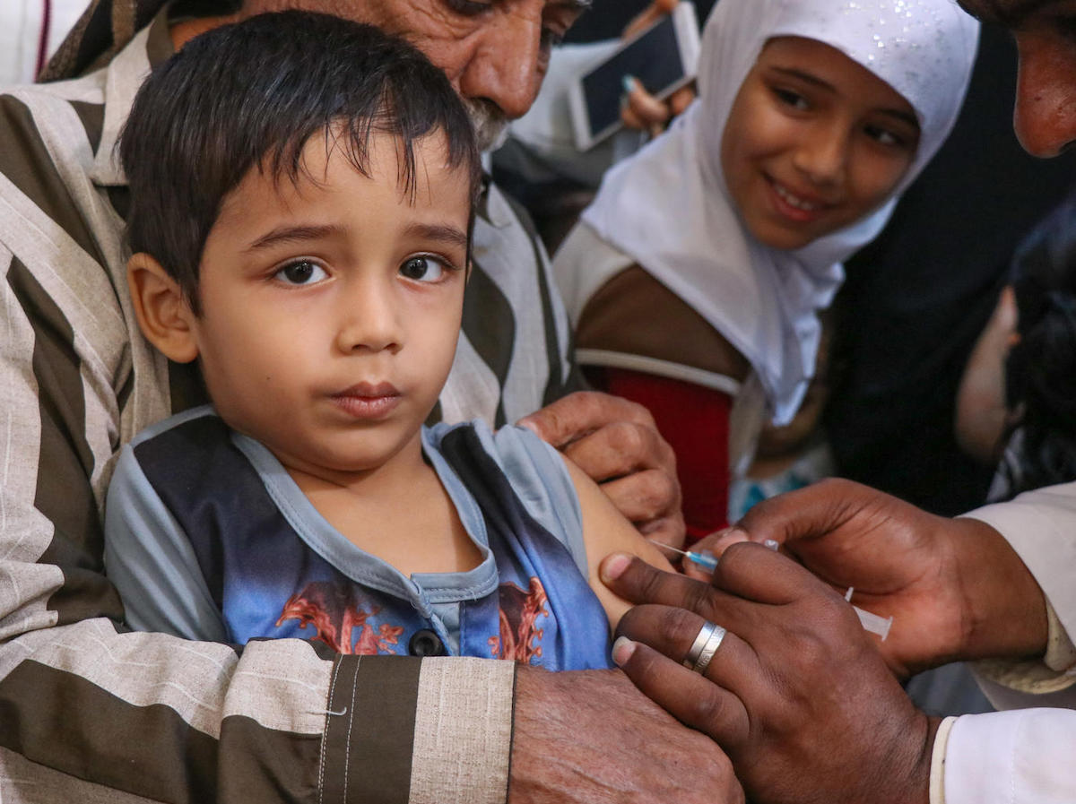 A boy receives a measles and rubella vaccine during a UNICEF-backed mobile vaccination campaign in Aden, Yemen in February 2019.