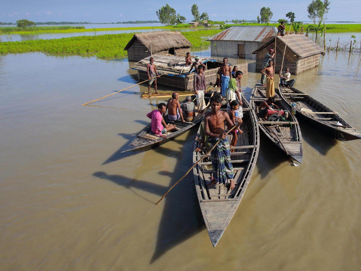 A family take to their boats after severe flooding in 2017 in the northern district of Kurigram, Bangladesh.