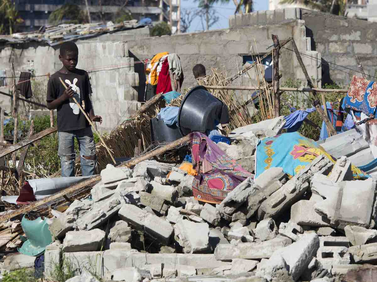 On 24 March 2019 in Mozambique, a boy stands near a destroyed house in an area that was flooded after Cyclone Idai made landfall in Beira.