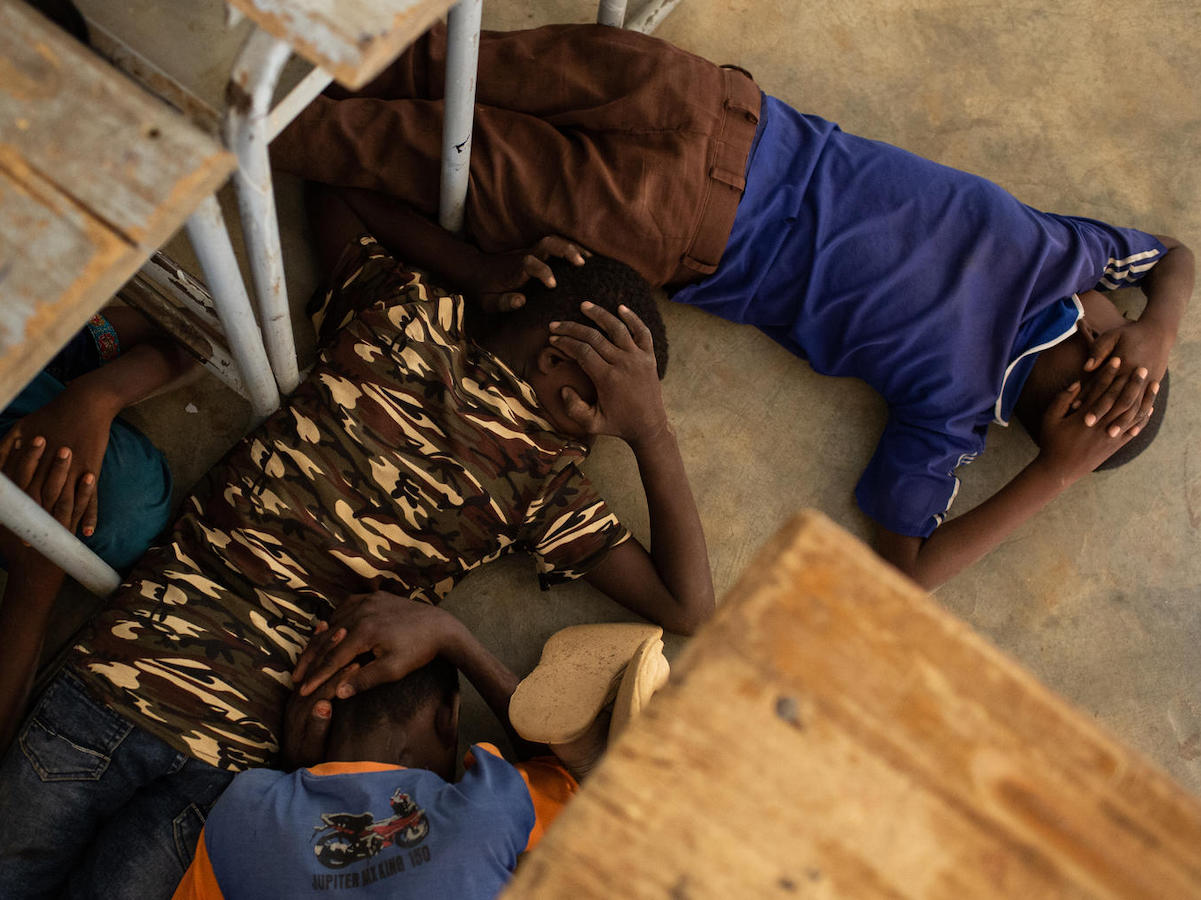On June 26, 2019, children take part in an emergency attack simulation at the Yalgho Primary School in Dori, Burkina Faso.