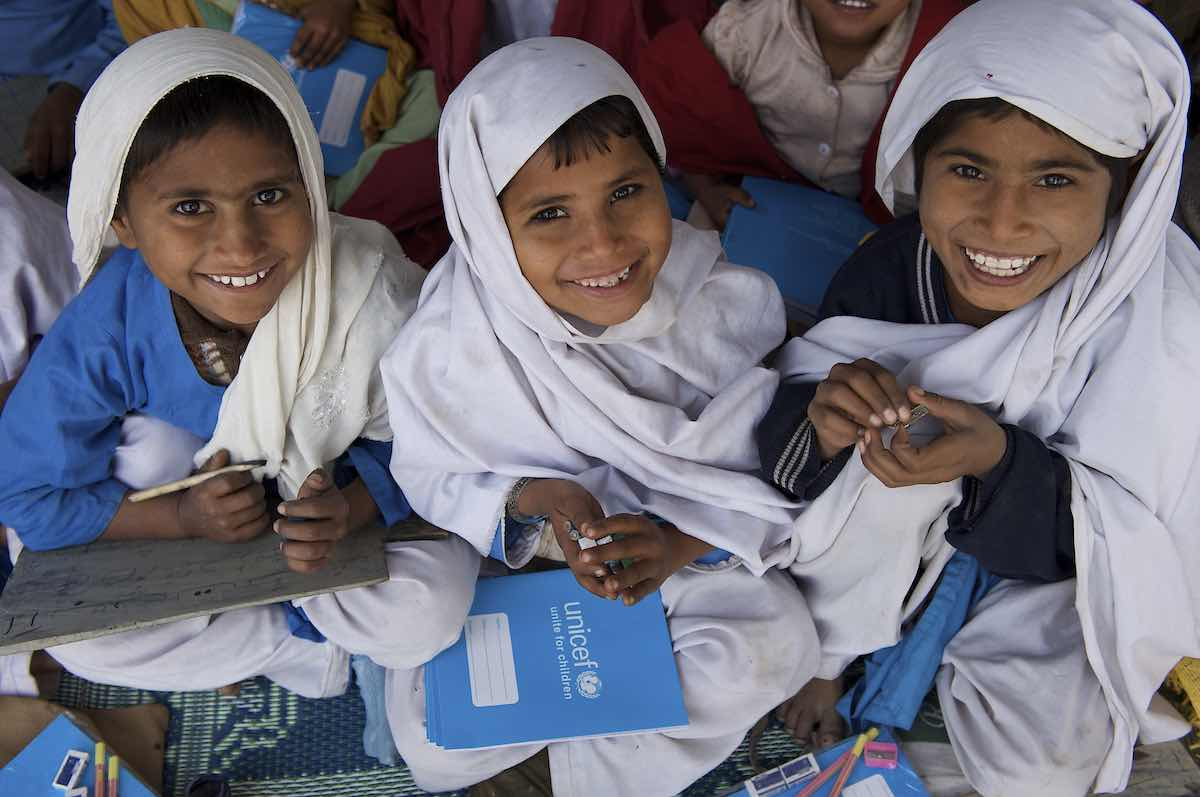 Children smile while attending school in a UNICEF-supported Temporary Learning Centre (TLC) in the village of Basti Bhaya in Rajanpur, amongst one of the worst affected district in Punjab province.