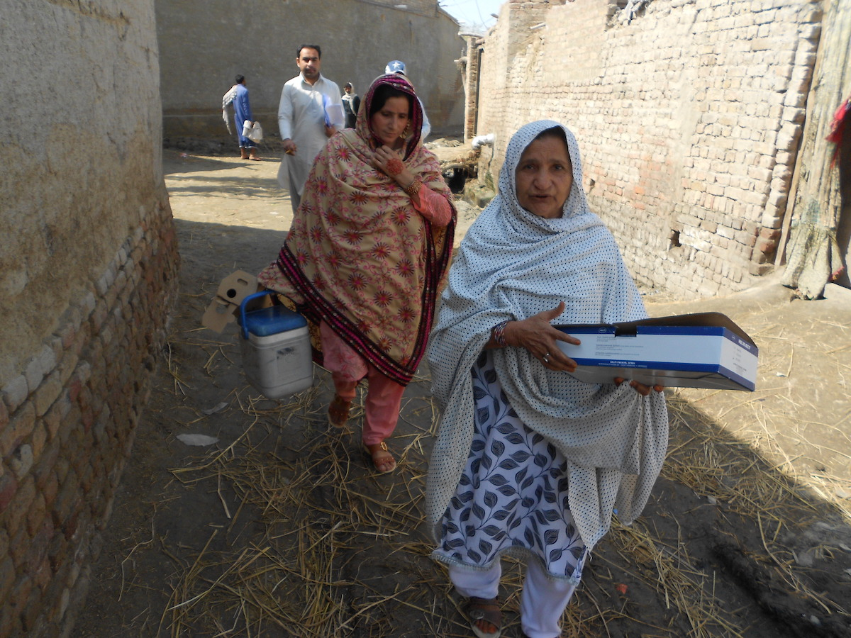 """In Pakistan's Kambar District, UNICEF-supported """"lady health workers"""" Jameela, right, and Shamul visit the village of Peer Go Goth to vaccinate women against tetanus."""