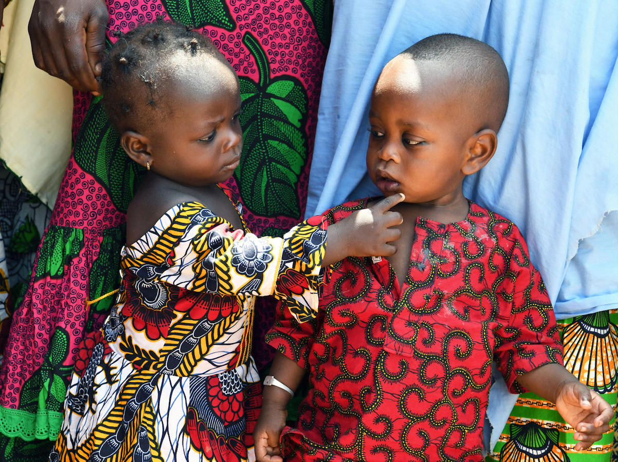 A young girl comforts her brother in Odienné, in northeastern Côte d'Ivoire.