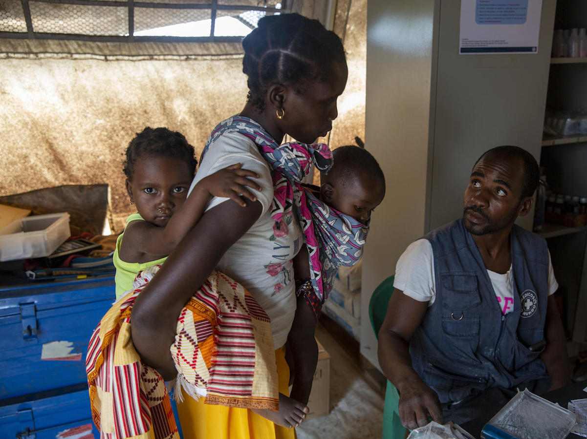 Eliza Arnaldo, 20, carries her children Natalia , 3, and Dominiqo, 6 months, to a UNICEF health center after they became feverish in the Ndjenja resettlement camp, Mozambique, March 4, 2020.