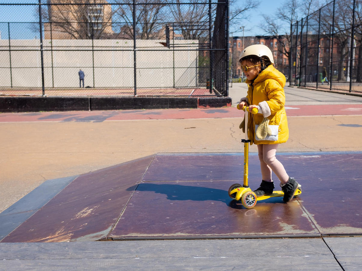 Margot, 4, rides her scooter in a park in New York City on March 26, 2020.