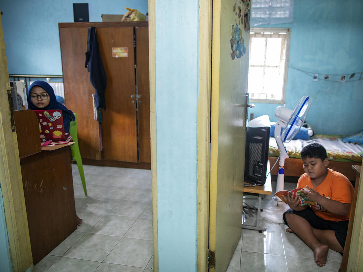 Elementary school student Arkan, 9, (right) studying at home and keeping a distance from his sister, Siwi, during the COVID-19 outbreak in Jakarta, Indonesia on March 29, 2020.