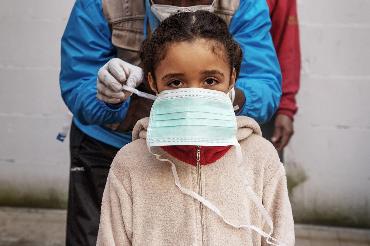 On 31 March 2020, seven-year-old Francesca [NAME CHANGED] is given a protective mask by INTERSOS/UNICEF outreach worker Abdoul Bassite, prior to a health screening in the informal settlement in Rome, Italy, where she lives.