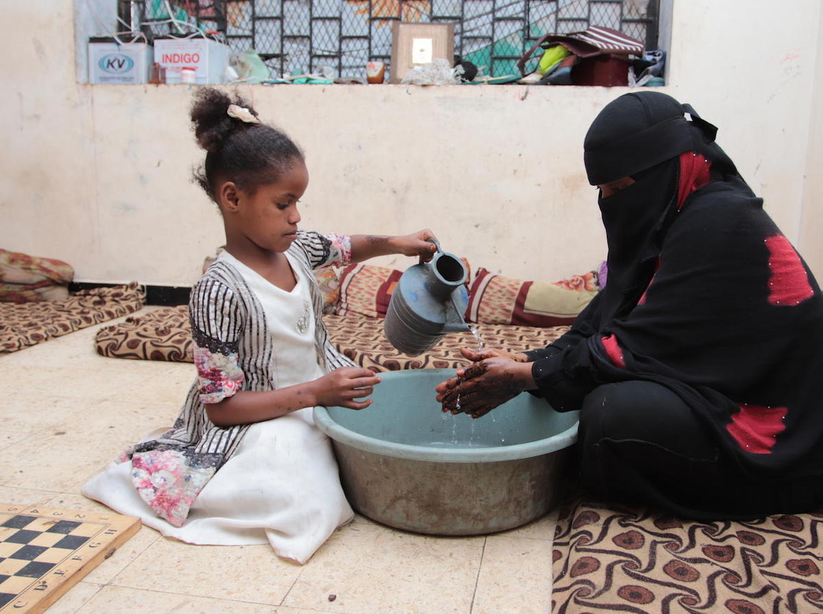 On 4 April 2020, Fatima pours water to help her mother wash her hands thoroughly, in a centre for internally displaced persons in Aden, Yemen.
