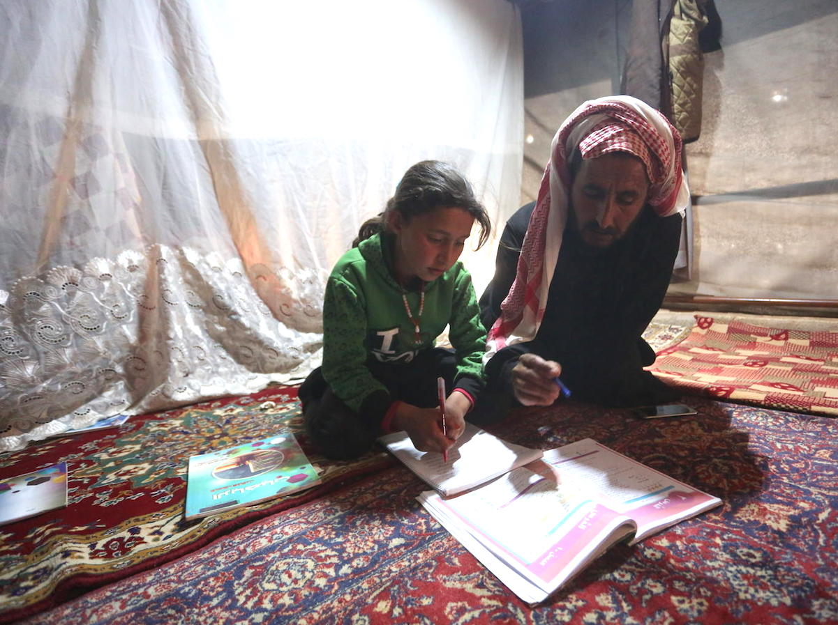 On 9 April 2020, 9-year-old Maria follows a pre-recorded lesson on her father's smartphone in a tent at the Kili IDP camp in rural Idlib.