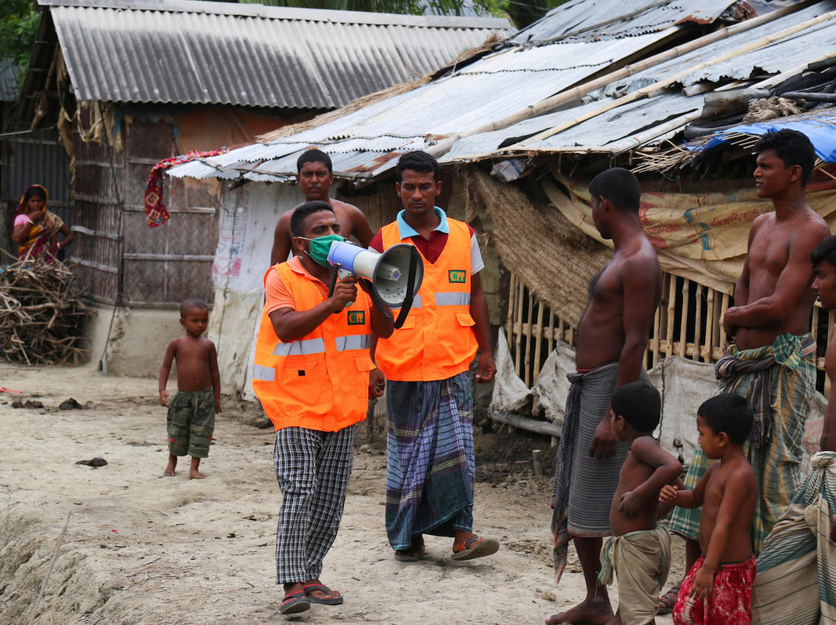 A UNICEF-supported Cyclone Preparedness Program (CPP) volunteer uses a megaphone to urge residents to evacuate to shelters ahead of the expected landfall of cyclone Amphan in Khulna, Bangladesh on May 19, 2020.