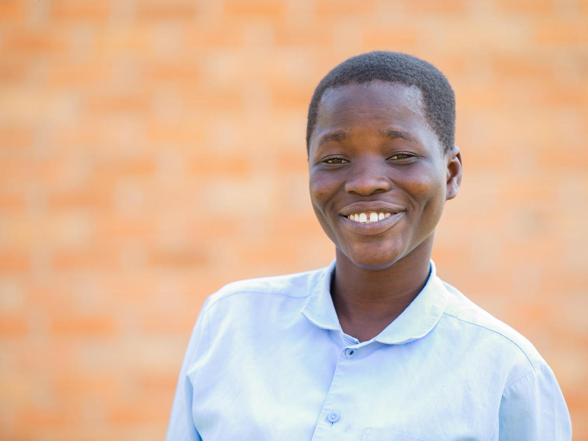 Nelia, 18, is on track to receive her secondary school diploma at Mpamba Community Day Secondary School in Nkhatabay District, Malawi, with help from a scholarship provided by the Kids in Need of Desks (K.I.N.D.) Fund.