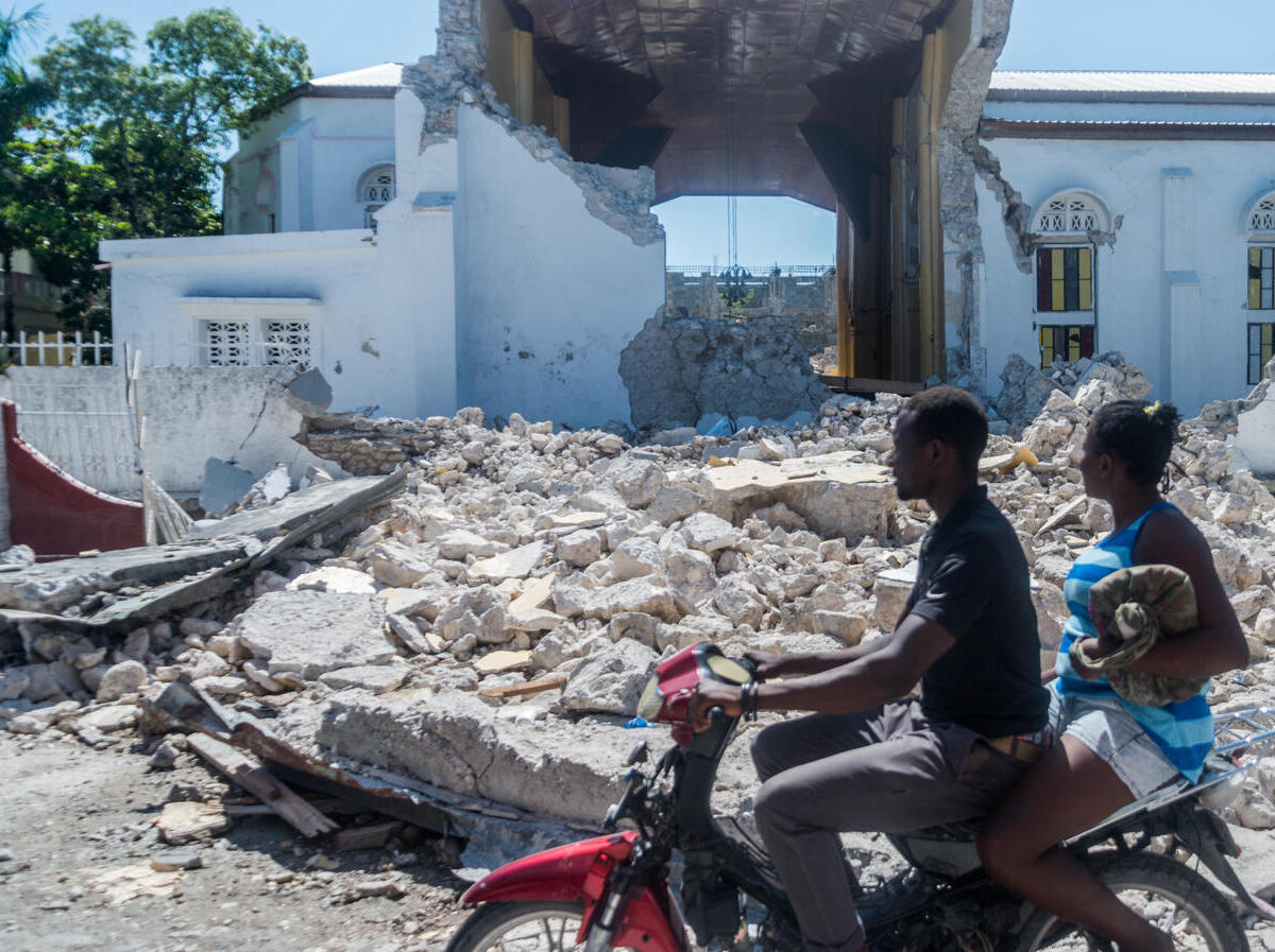 People drive past the remains of the Sacré Coeur des Cayes church in Les Cayes on August 15, 2021, after a 7.2-magnitude earthquake struck Haiti's southwest peninsula.