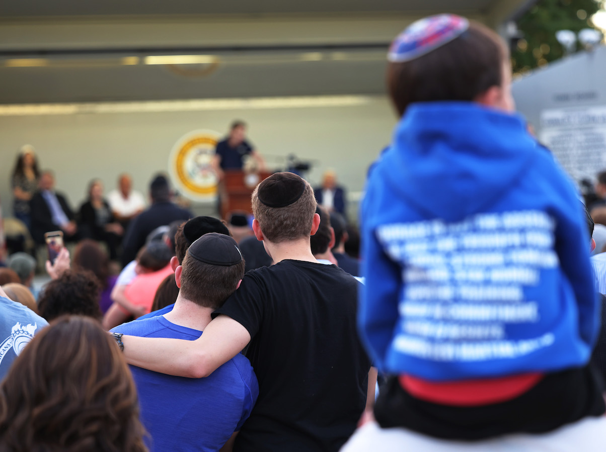 People listen to Joseph Borgen, a recent victim of a hate crime, speak during a rally denouncing antisemitic violence on May 27, 2021 in Cedarhurst, New York.