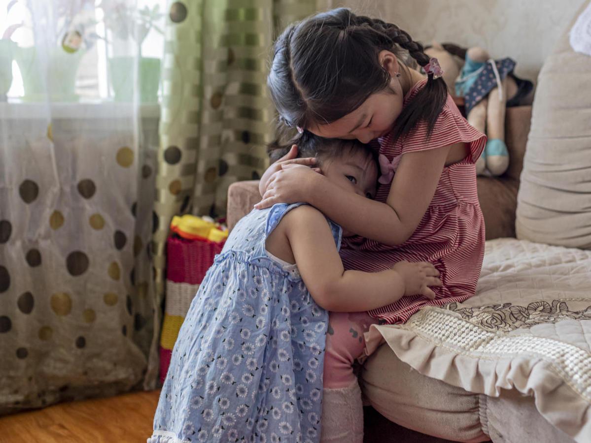On May 20, 2019, Uuriintsolmon Erdenejargal, 1, cuddles with her older sister, Gunjidmaa Nyambat, 5, at their home in Murun, Khövsgöl province, Mongolia.