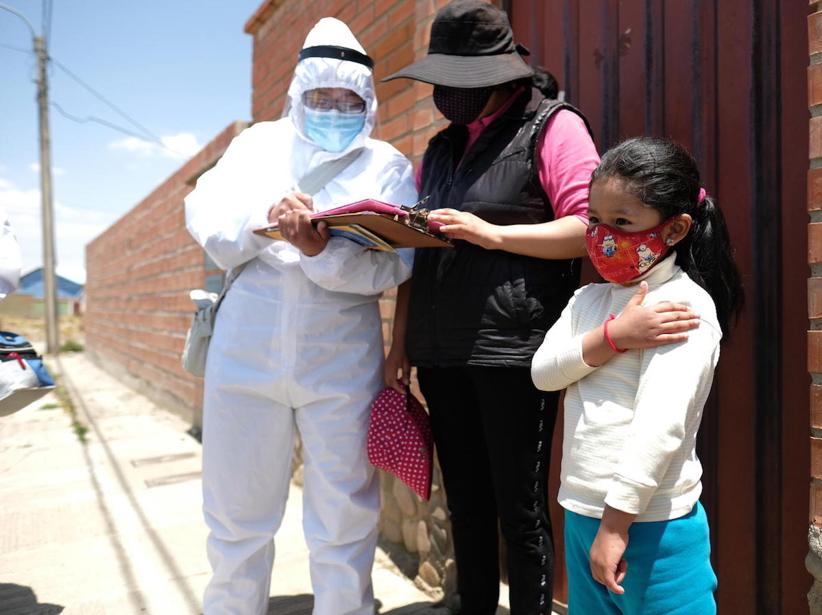 On October 13, 2020 in El Alto, Bolivia, 6-year-old Noelia gently touches her arm where she received a flu shot from a member of aUNICEF-supported vaccination team that goes door-to-door.