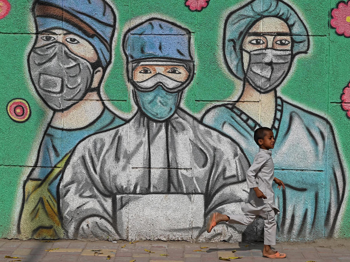 On March 21, 2021 in India, a child runs past a mural depicting frontline health care workers, along a road in New Delhi.