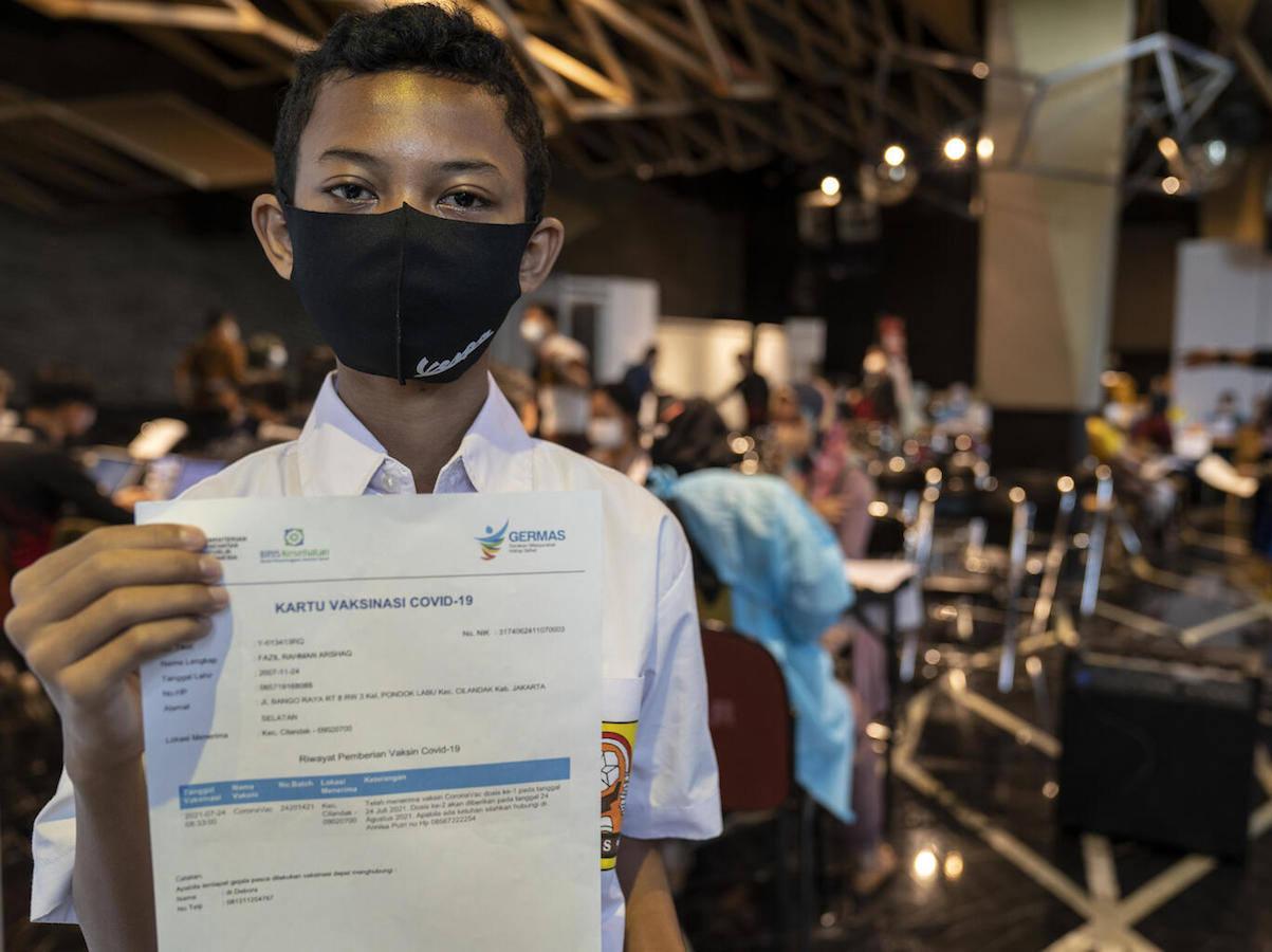 Fazil, 14, shows his certificate after receiving his second dose of COVID-19 vaccine at the Cilandak Town Square Mall in South Jakarta, Indonesia, on August 24, 2021.