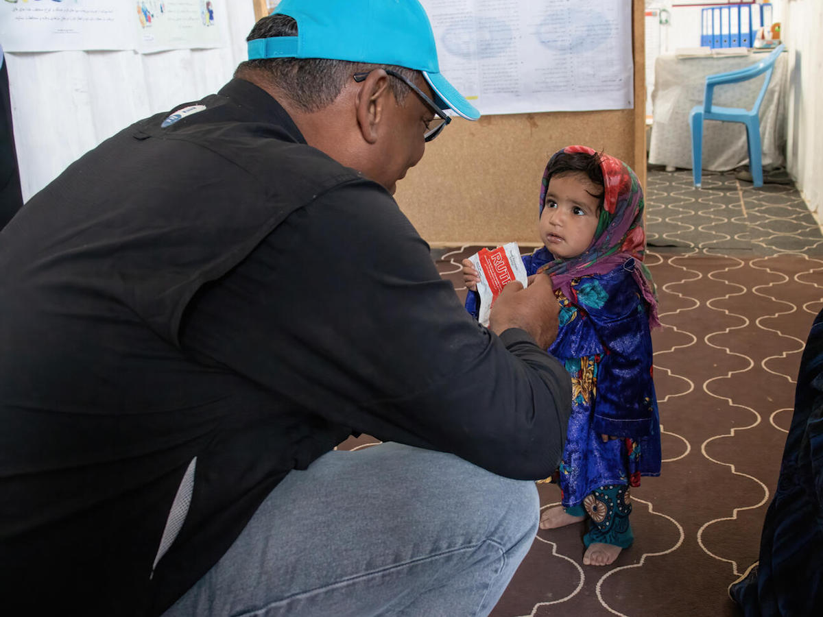 UNICEF Representative in Afghanistan Hervé Ludovic De Lys greets a girl enjoying a packet of Ready-to-Use Therapeutic Food at a clinic in the Sabz-e-Shark IDP camp in Herat on September 29, 2021.