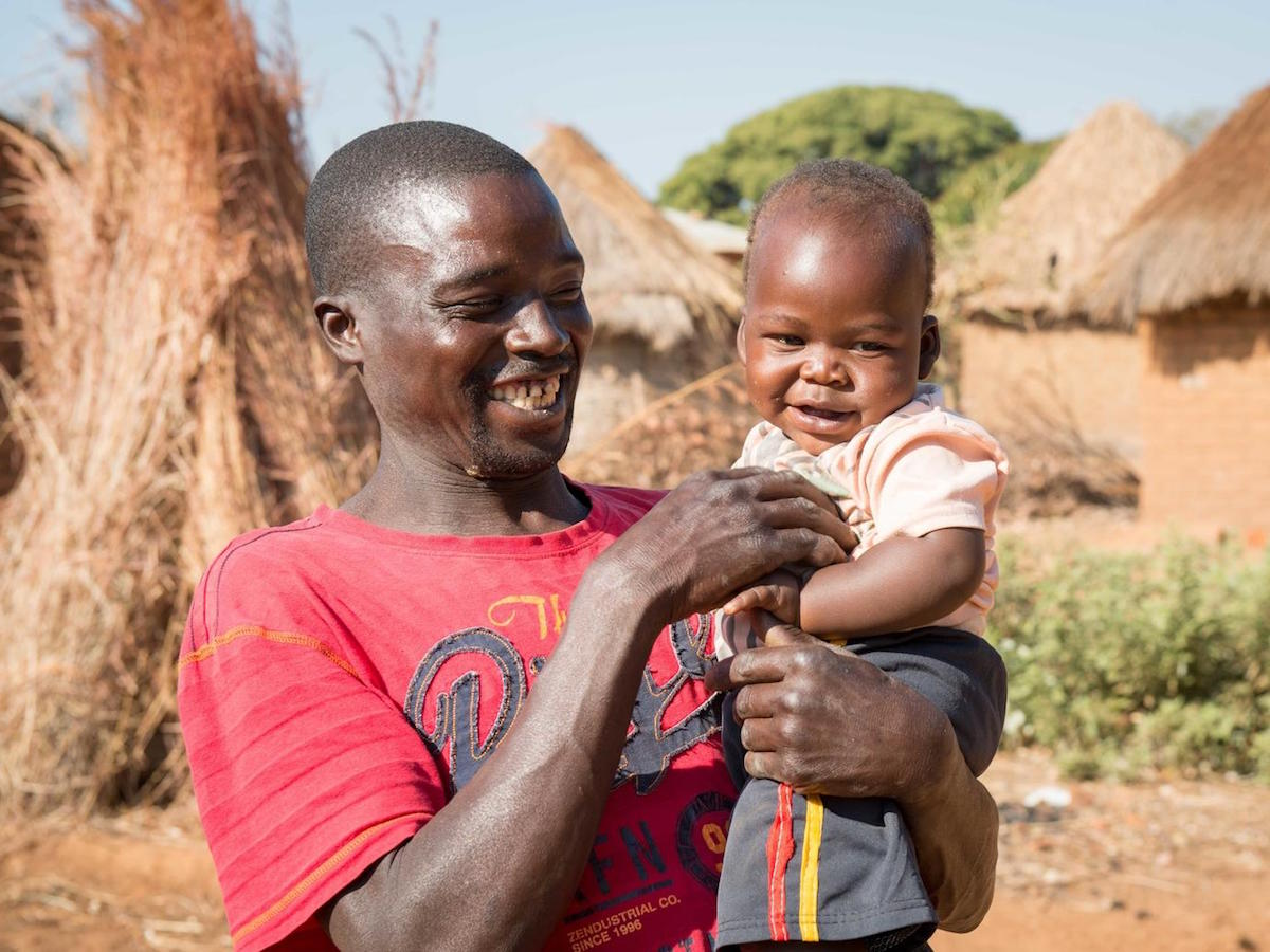 One-year-old baby Moses and father Ponsilio Phiri playing in Zambia in 2020. Baby Moses is enrolled in the LEGO Playful Parenting program implemented by UNICEF.