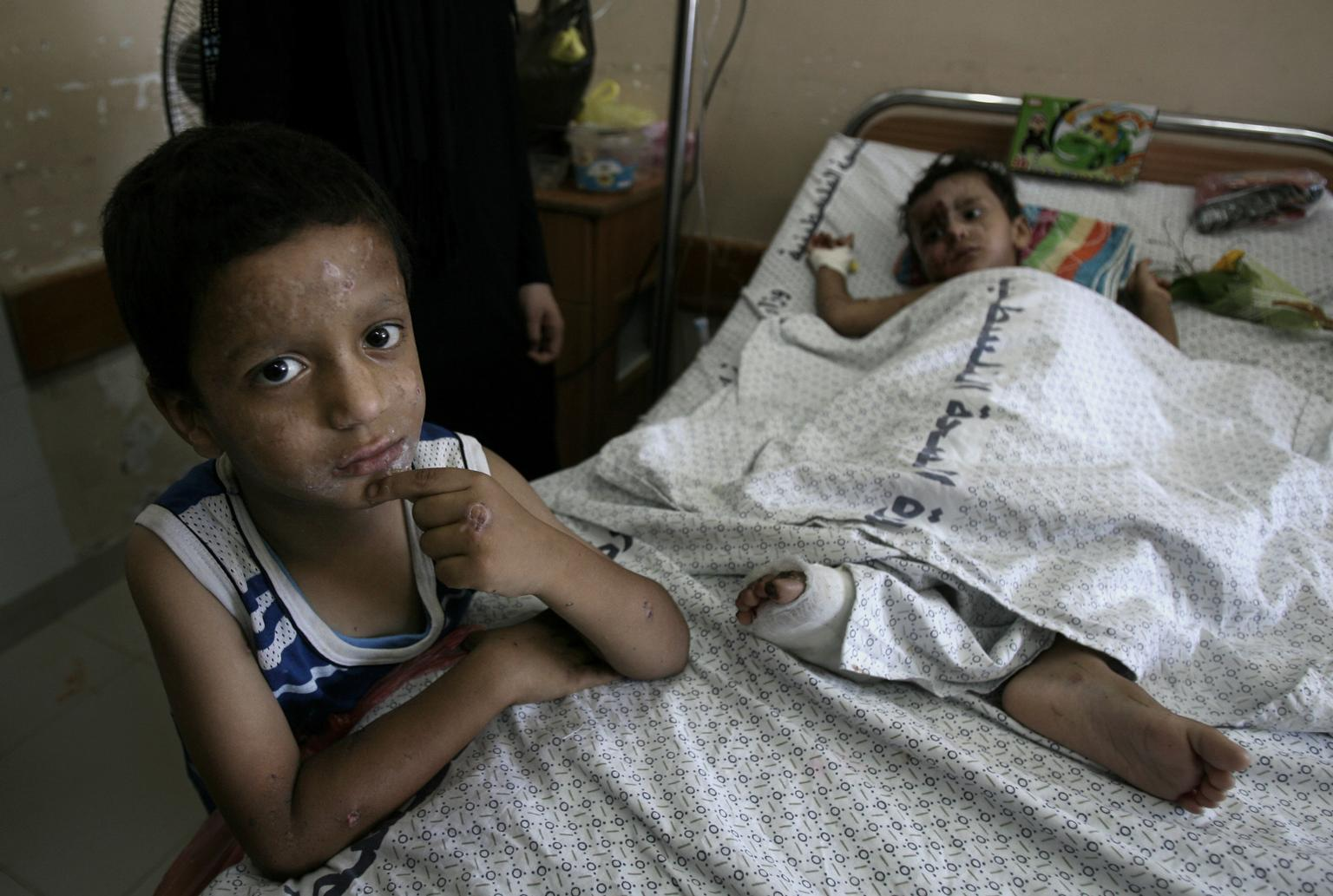 Moussab Wahdan, 5, stands beside the cot on which his 18-month-old brother, Mohammed Ali Wahdan, lies in the paediatric ward of Al-Shifa Hospital, Gaza.