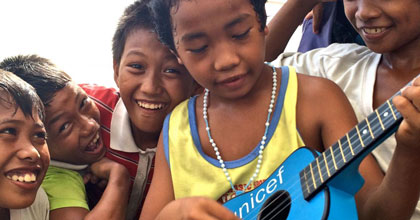 Boys smile at the camera while one plays on a UNICEF guitar in the Philipines.