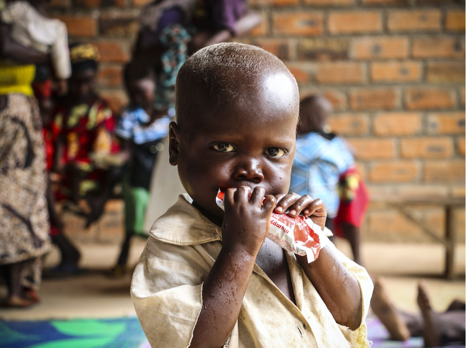 At a UNICEF-supported treatment center outside Bangui, Central African Republic, a young boy is given Ready-to-Use Therapeutic Food, a highly-effective treatment for severe acute malnutrition.