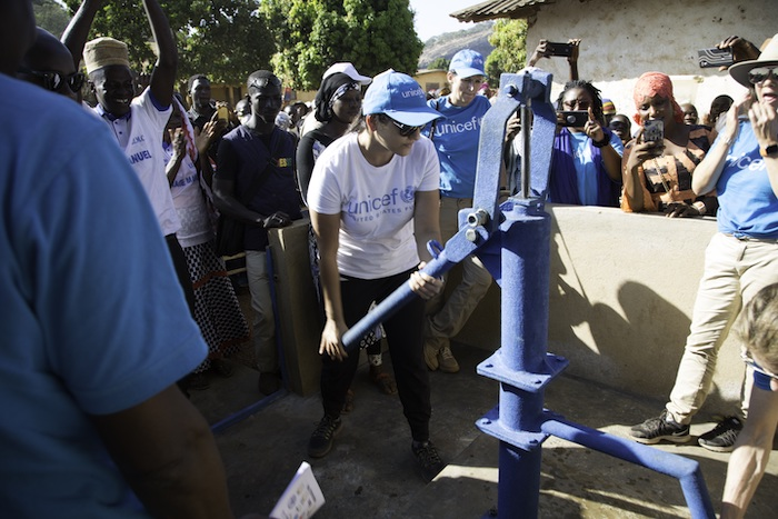 Dr. Sippi Khurana, UNICEF USA Houston regional board chair, tests a new safe water access point provided through UNICEF's Water for Guinea program during a recent field visit.