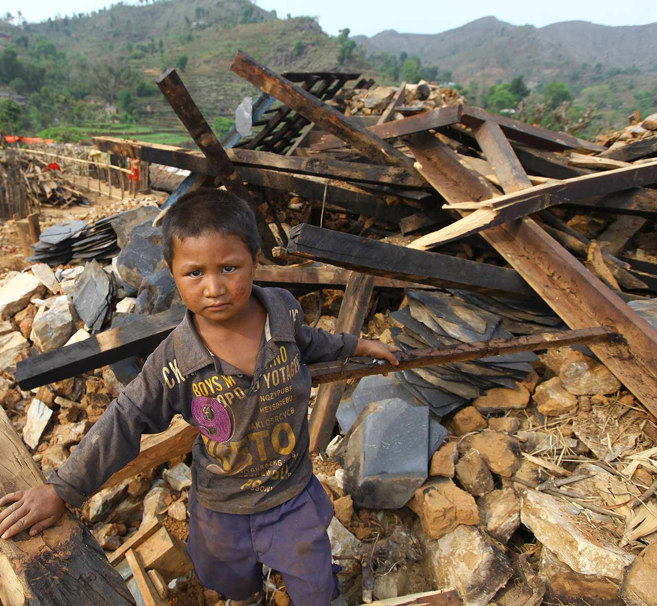 A young boy stands on the rubble of a destroyed home in central Nepal. Donation Form Background