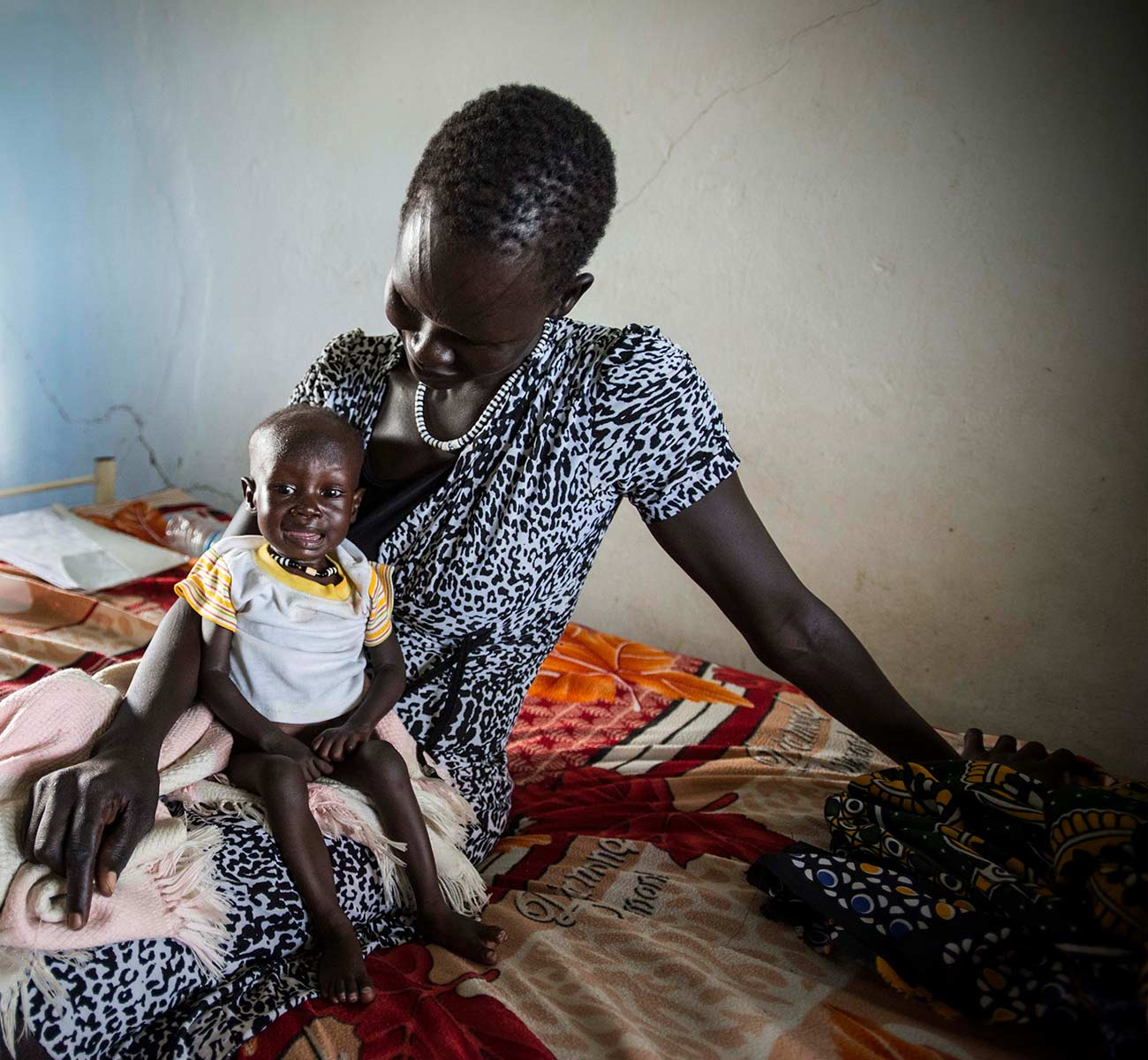 A South Sudanese mother holds her troubled child - Donation Form Background