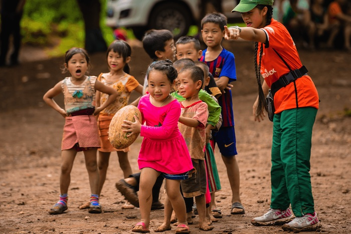A coach teaches kids teamwork through sport in a village in Laos.