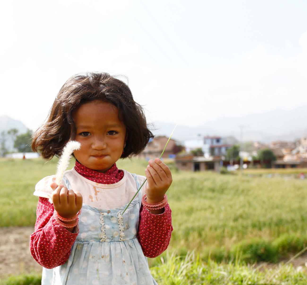 A girl in Nepal holds up a blade of grass and what could be either a feather or a grass flower with mountains and a town in the background