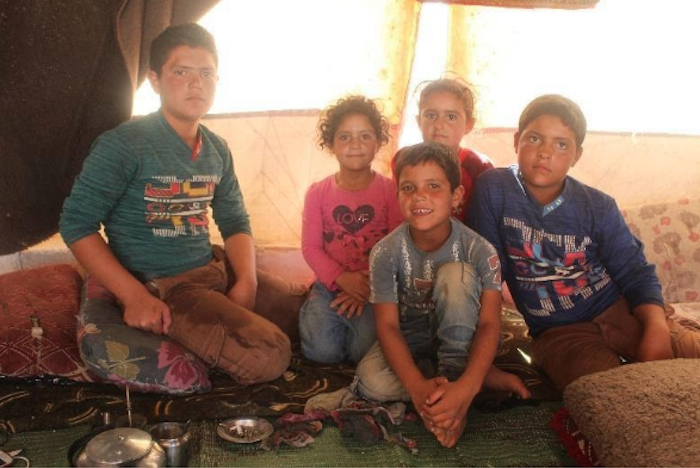 Hasan, 8, front and center, and his four siblings live in a camp for displaced persons in northern Idlib, Syria, where they have access to a self-learning program supported by UNICEF.