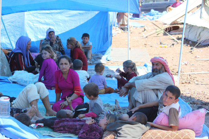 Yazidi children and families rest and shelter from the sun at Nawrouz refugee camp. © UNICEF Syria/2014/Razan Rashidi